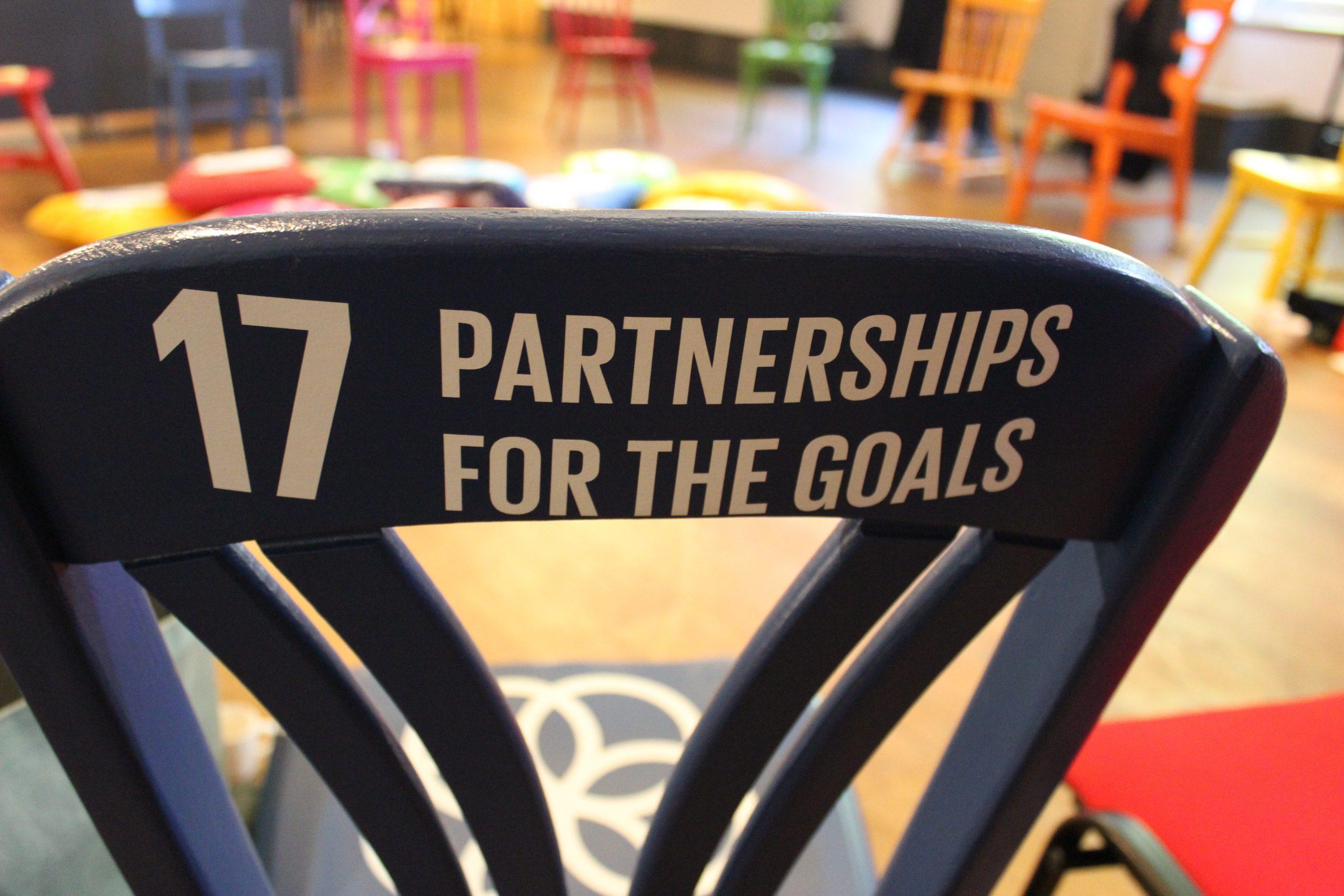 SDG 17 partnerschap om de doelstellingen te bereiken gedrukt op de rugleuning van in dezelfde kleur stoel