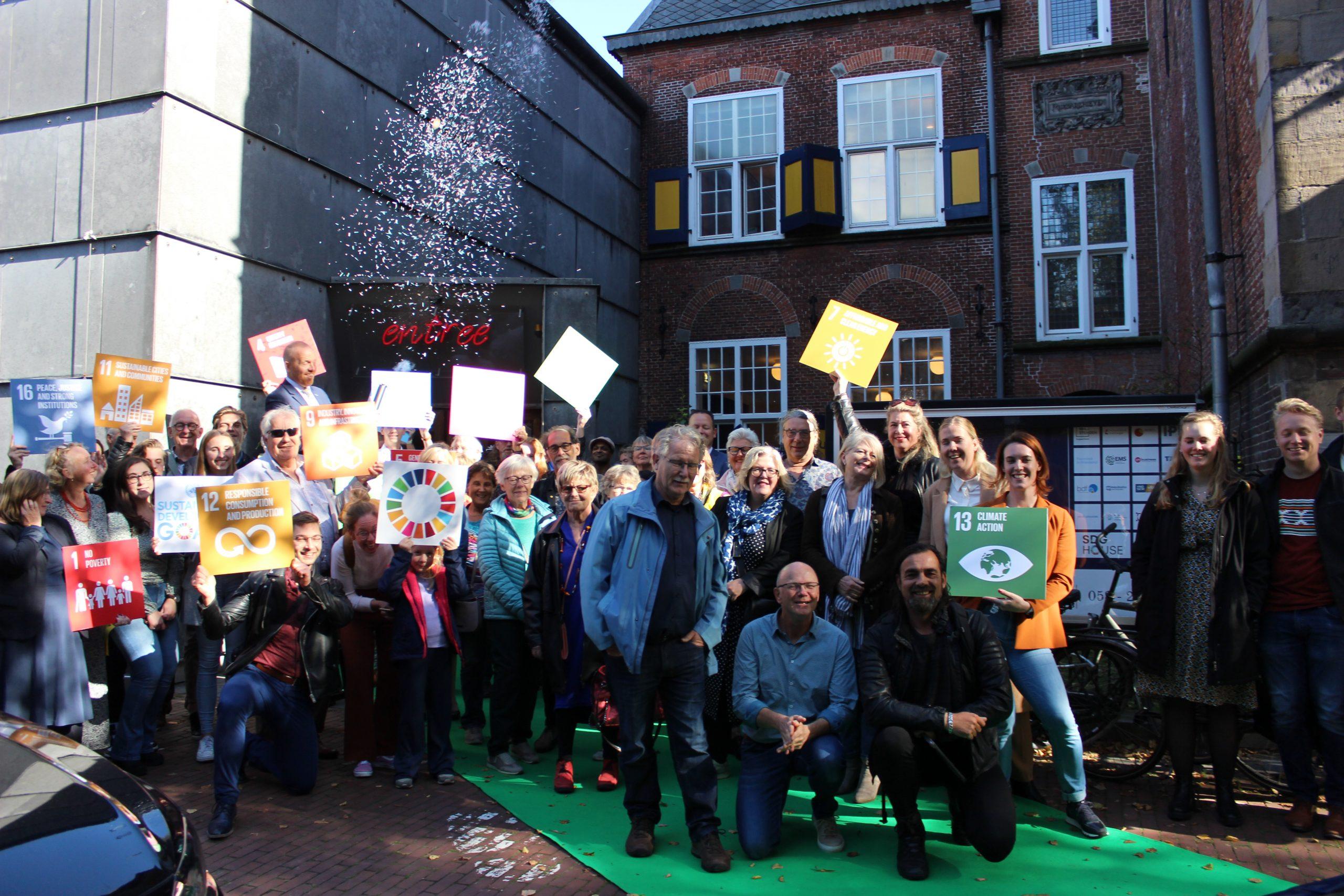 Het publiek staat juichend met SDG borden in de lucht voor de Kanselarij bij de opening van de SDG House Fryslân met duurzaam confetti